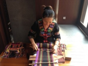 Local lady weaving, the warp held taut on her feet