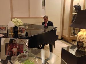 A pianist plays, day-long, at the rear of the lobby