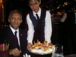 St Regis Singapore's general Manager Ananda Arawwawela is offered mini burgers during the Astor Bar's cocktail hour