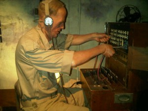 The telephone 'operator' leans forward, his arm pushing wires into sockets