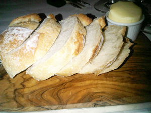 Simple style - great bread, hand-sliced, on a wood board with silver edging