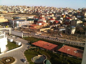 From suite 1405, look down to hotel's gardens, with tennis court, and across M. Mushfig Street to residential areas