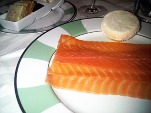 Smoked salmon on a porcelain plate, and lemon in a little 'hat'