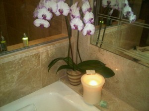 At the Four Seasons Singapore luxury hotel the bathtub is guarded by fresh orchids and big candles