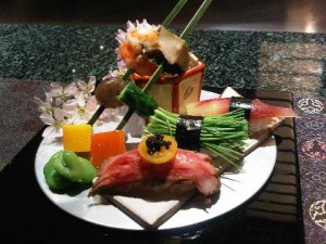 Starter plate, with a pair of skewered morsels and, on right three sushi