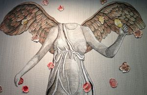 Nearby, an embroidered angel has lost her head