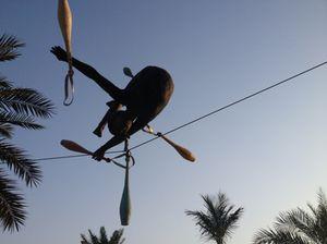 A Jotka sculpture hangs between trees...