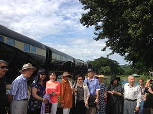 Posing in front of the train on the River Khwai bridge, passengers...