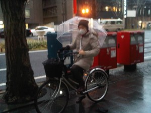 Japanese woman cycling in the rain, umbrella and telephone in hand