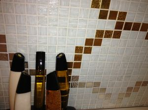Towers-shaped toiletries against a bathroom's marble-tiled wall