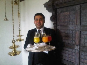 A butler welcomes you with drinks at Taj Mahal Delhi luxury hotel in India