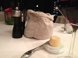 Simplicity of bread in a sack, and butter on a china plinth