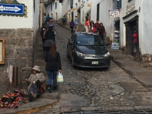 A typical street, angled, cobbled, women sitting, traffic...