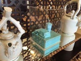A pair of decorative teapots flank a Tiffany display