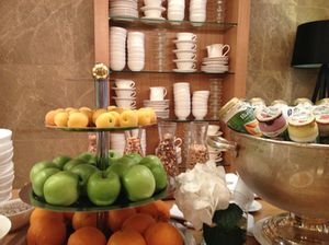 The breakfast buffet is in front of a wall of stacked china