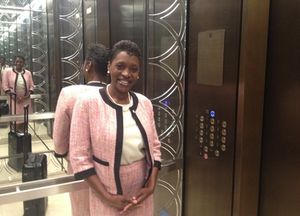 Hostess in a Langham-pink Chanel suit