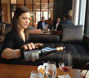 The server crouches as she pours wine