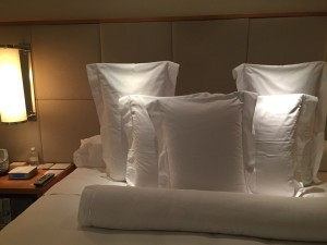 The bed's pillows interestingly sit upright