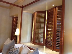 Behind the outline-only four-poster, shutters open to the bathtub