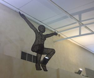 A wire figure flies over the gym