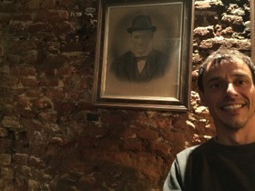 Michael of the Gin Bar in front of his grandfather's photo